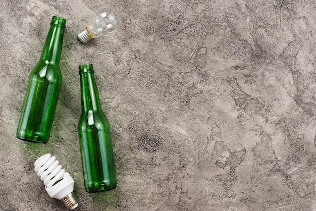 Bottiglie vuote verdi e lampadine usate