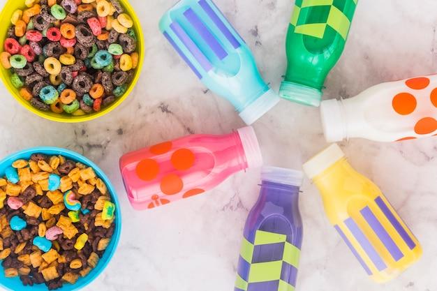 Bottigliette per il latte con ciotole di cereali sul tavolo