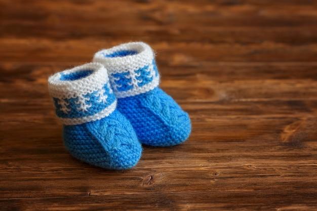 Bottini fatti a mano blu del bambino all'uncinetto su fondo di legno