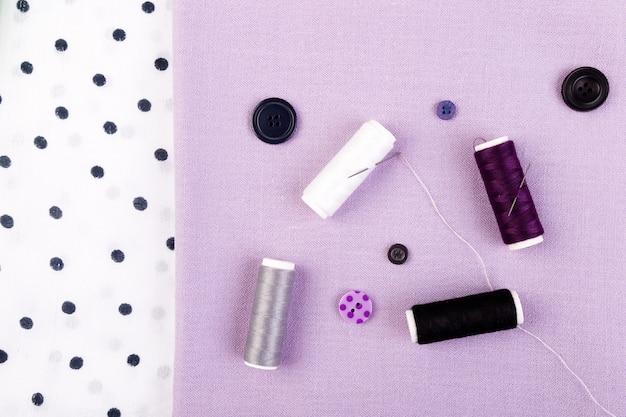 Bottoni da cucire, rocchetti di filo e stoffa sul tavolo di legno