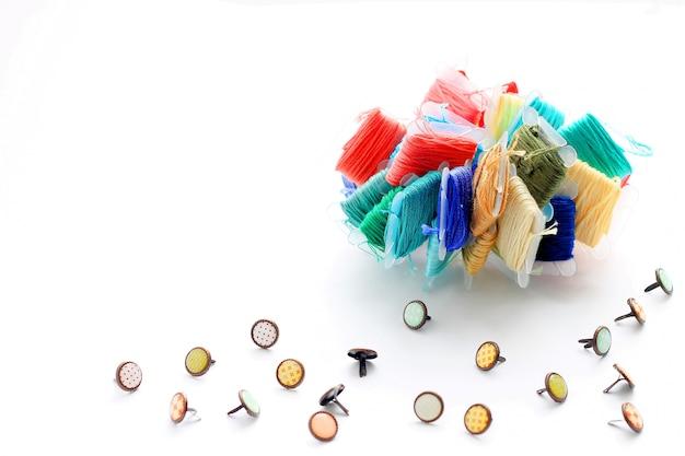 Bottoni decorativi e un set di fili per il ricamo.
