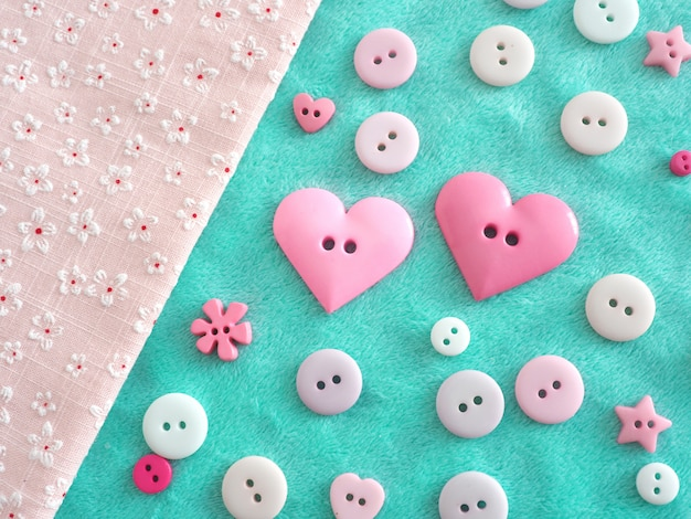 Bottoni di varie dimensioni di tonalità pastello e due pulsanti a forma di cuore