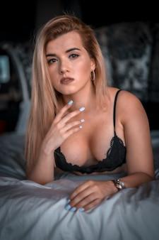 Boudoir e sessuale giovane donna bionda caucasica in lingerie nera sulla cima di un letto rotondo. con sguardo sessuale