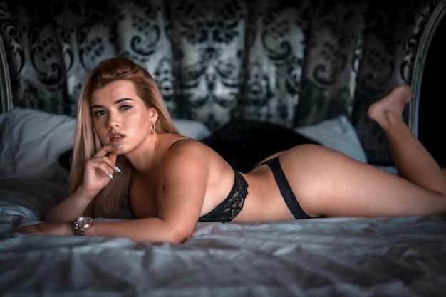 Boudoir e sessuale giovane donna bionda caucasica in lingerie nera sulla cima di un letto rotondo. sdraiato sul letto a faccia in giù. con uno sguardo seducente