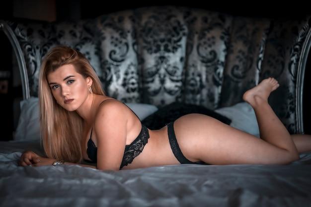 Boudoir e sessuale giovane donna bionda caucasica in lingerie nera sulla cima di un letto rotondo. sdraiato sul letto a faccia in giù. con uno sguardo serio e seducente