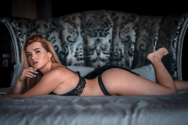 Boudoir e sessuale giovane donna bionda caucasica in lingerie nera sulla cima di un letto rotondo. sdraiato sul letto a faccia in giù. con uno sguardo serio
