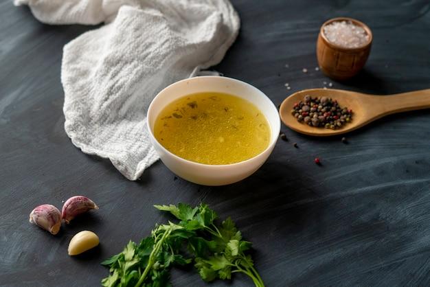 Boullion fatto in casa o zuppa chiara in una ciotola di ceramica in cucina, cibo sano e diete