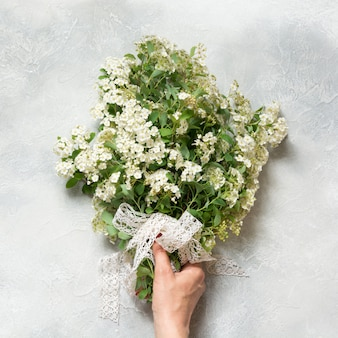 Bouquet bianco spirea fiori in mano femminile