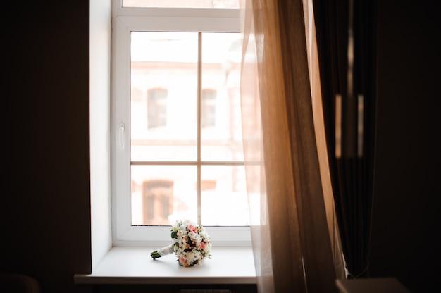 Bouquet da sposa bella di fiori sul davanzale della finestra