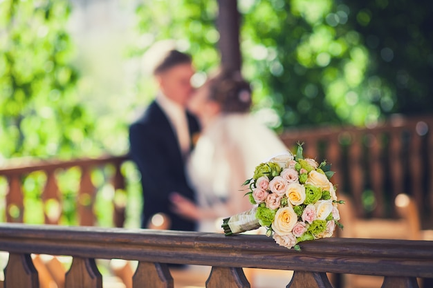 Bouquet da sposa bella sullo sfondo di baciare la sposa e lo sposo
