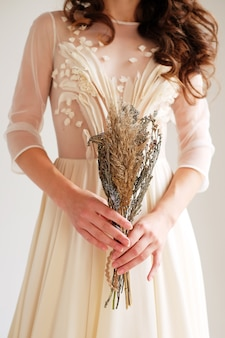 Bouquet da sposa con fiori secchi e spighette stile boho nelle mani delle spose