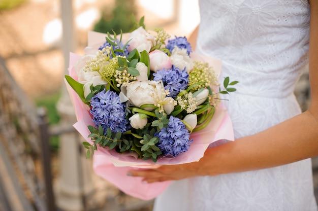 Bouquet da sposa con pioni nelle mani della sposa