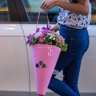 Bouquet da sposa di cardi e fiori di filo interdentale tenuti da una ragazza in jeans