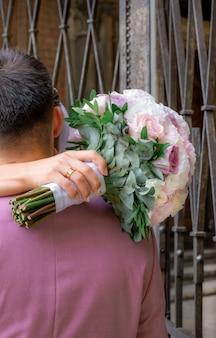 Bouquet da sposa di rose rosa, bianche e lilla in mano alla sposa.