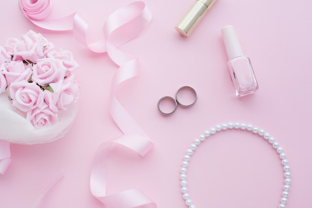 Bouquet da sposa di rose rosa, fedi nuziali, collana, smalto e nastro rosa