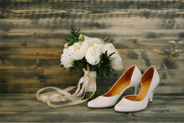 Bouquet da sposa e scarpe da sposa su uno sfondo di legno
