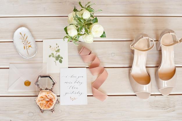 Bouquet da sposa elegante con un nastro, invito a nozze, anelli e scarpe da sposa su tessuto.