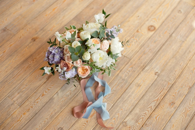 Bouquet di close-up di rose peonie fresia dianthus fiori sul pavimento bianco rotondo al chiuso