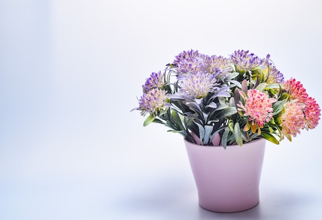 Bouquet di fiori colorati in un vaso su un grigio.
