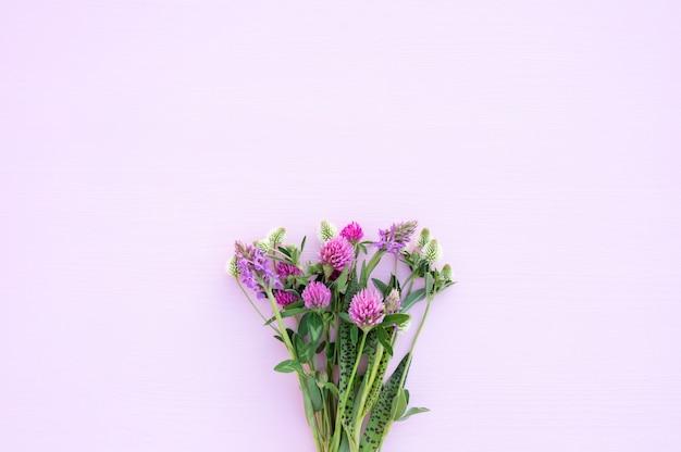 Bouquet di fiori di campo su un rosa chiaro
