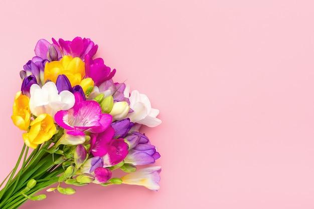 Bouquet di fiori di fresia rametto isolato su sfondo rosa biglietto di auguri floreale vista dall'alto piatto lay