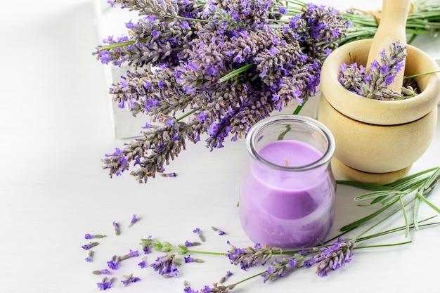Bouquet di fiori di lavanda, mortaio di legno con pestello e candela di lavanda closeup. concetto di aroma di erbe.