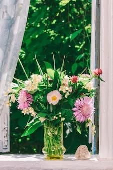 Bouquet di fiori di trifoglio, fiordalisi e gelsomino in un vaso di vetro e una pietra a forma di cuore