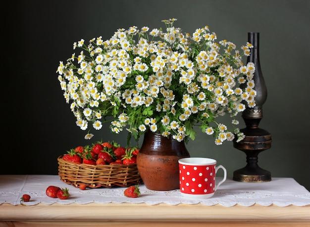 Bouquet di fiori e frutti di bosco in un cesto su un tavolo con una tovaglia di pizzo.