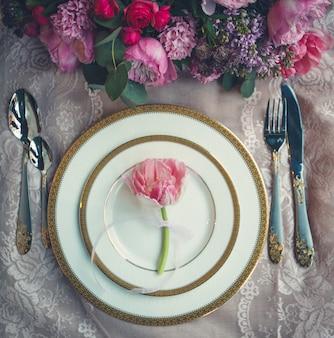 Bouquet di fiori e singolo tulipano rosa all'interno di piatti bianchi.