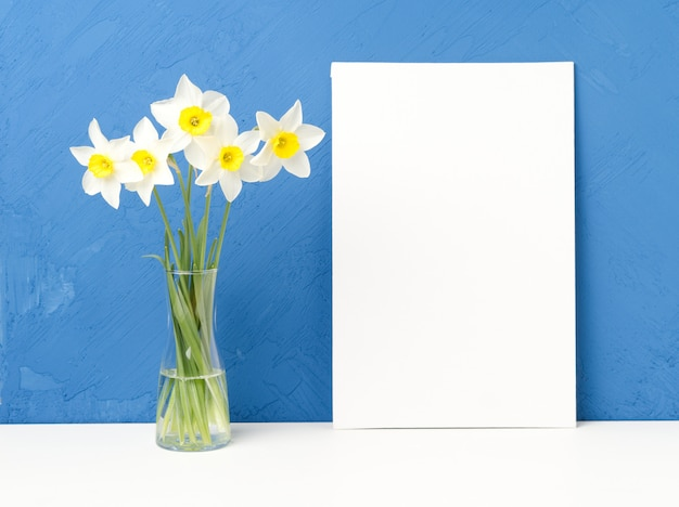 Bouquet di fiori freschi, carta bianca vuota su un tavolo bianco