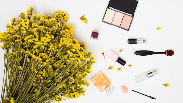 Bouquet di fiori giallo limonium; bottiglia di smalto per unghie; bottiglie di profumo; pennello per rossetto e trucco e cipria compatta su sfondo bianco