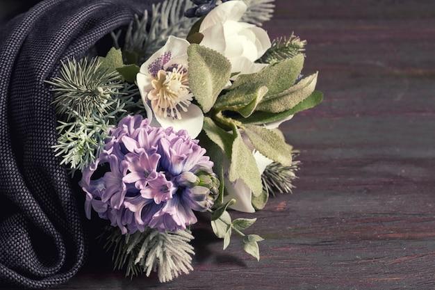 Bouquet di fiori in stile invernale con giacinto blu, anemoni bianchi e rami di albero di natale