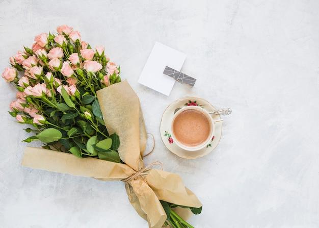 Bouquet di fiori rosa; carta e tazza di caffè su sfondo concreto