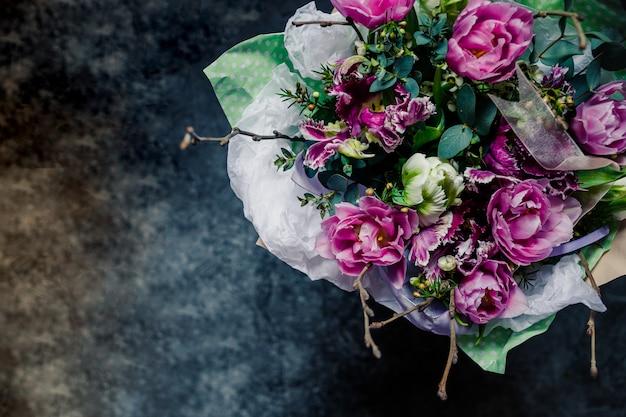 Bouquet di fiori sbocciante colorato molto bello di rose fresche di quicksand, garofani, ranuncoli, peonia, rami