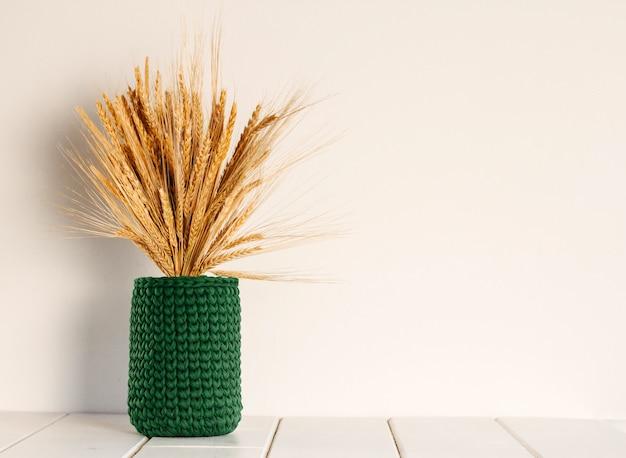 Bouquet di grano secco e segale in un vaso a maglia verde su un muro bianco