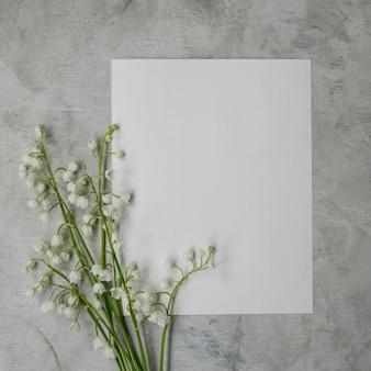 Bouquet di mughetti su sfondo grigio con un foglio bianco di carta bianca.