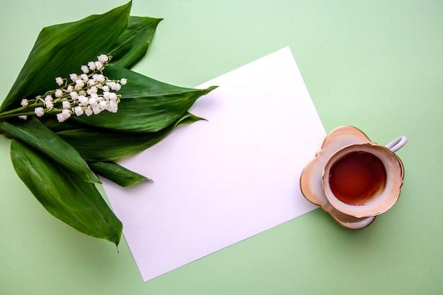 Bouquet di mughetti, una tazza di tè e un foglio di carta