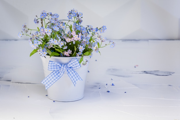 Bouquet di nontiscordardime in secchio di metallo con fiocco. concetto di primavera.