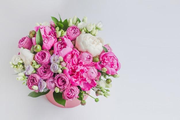 Bouquet di peonie, eustoma, spray rose in una scatola rosa con un'oasi