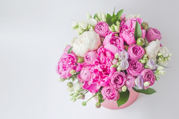 Bouquet di peonie, eustoma, spray rose in una scatola rosa