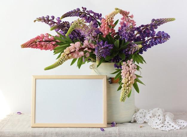 Bouquet di peonie rosa e viola in una lattina e una cornice rettangolare vuota sul tavolo.