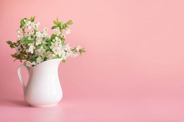 Bouquet di rami di fiori di ciliegio in vaso su rosa pallido pastello.