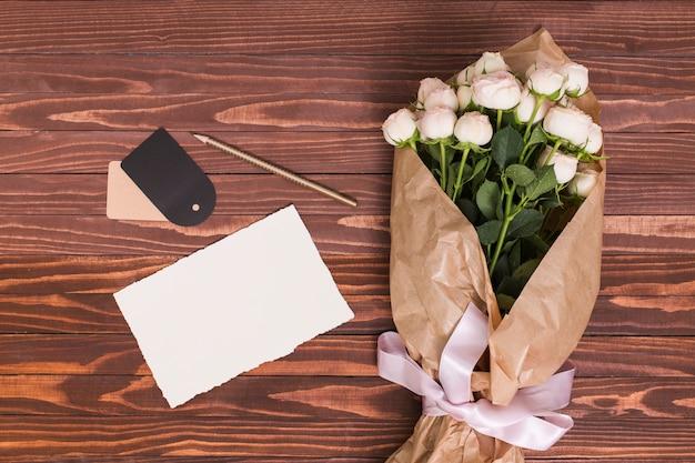 Bouquet di rose bianche; foglio bianco; matita e cartellino del prezzo su sfondo in legno