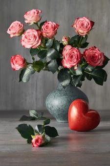 Bouquet di rose rosa e un cuore di pietra rossa sul buio