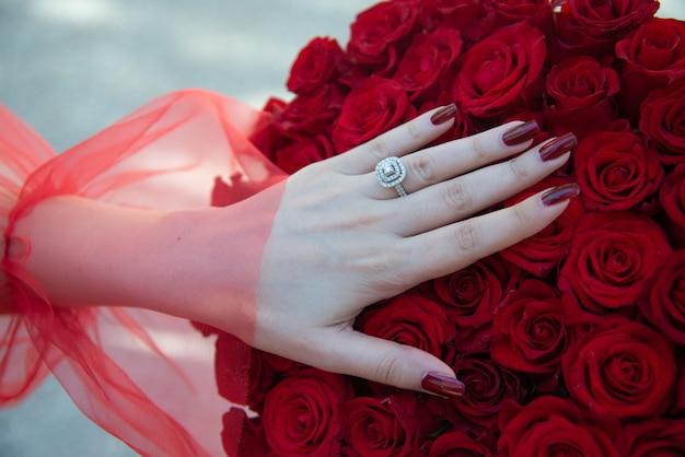 Bouquet di rose rosse con anello di fidanzamento. sposa con bouquet di fiori e anello di fidanzamento.
