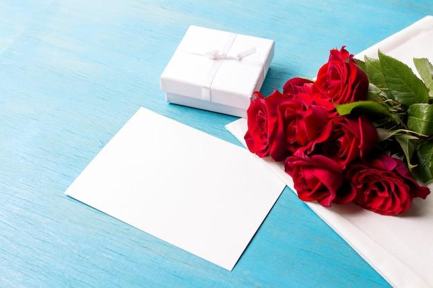 Bouquet di rose rosse confezione regalo bianca foglio pulito, fondo di legno blu. copia spazio. regalo romantico per le vacanze di san valentino