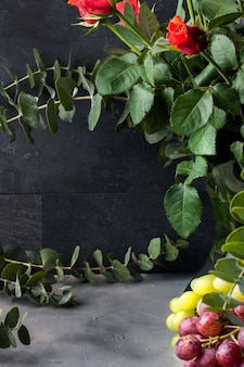Bouquet di rose rosse e un sacco di foglie verdi in un vaso su uno sfondo nero