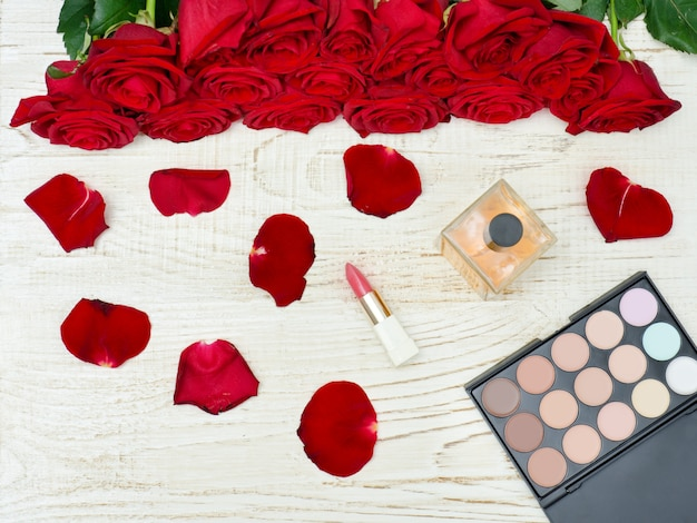 Bouquet di rose rosse, profumo, rossetto e palette di ombretti su un tavolo di legno bianco.