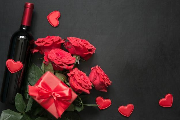 Bouquet di rose rosse, regalo, bottiglia di vino rosso sul tavolo nero.