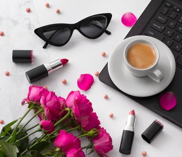 Bouquet di rose, tazza di caffè, laptop, occhiali da sole e rossetto sul tavolo bianco.